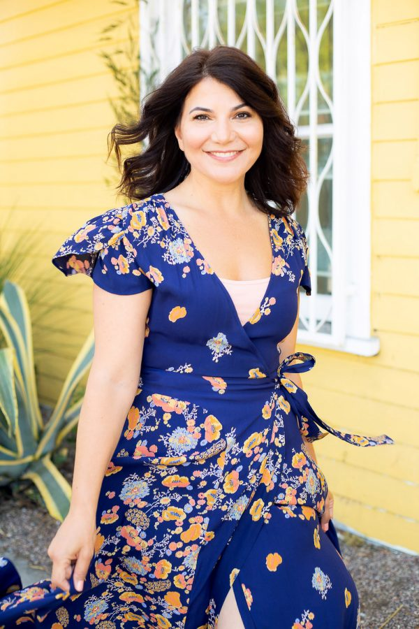 Actress Cindy Chavez smiling in front of yellow building Abbot Kinney