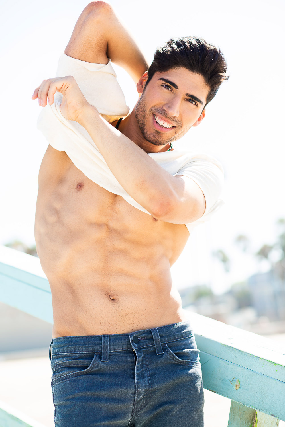 Male Latino model taking off shirt at Venice Beach