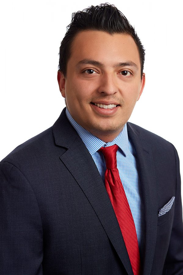 Corporate headshot of Latino in navy suit