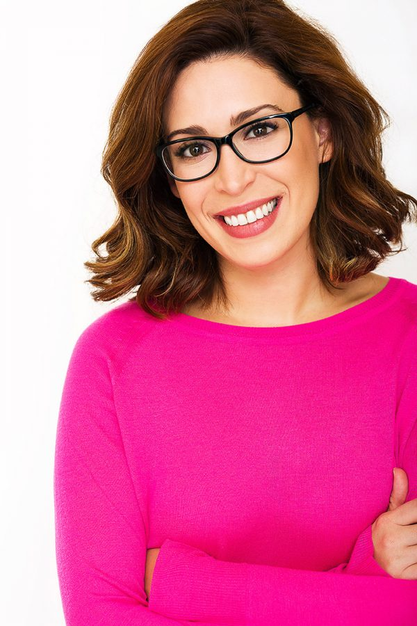 Smiling woman in glasses and pink sweater